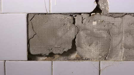устаревший : Interior of an old house cracked ceramic tiles falling off from the wall in the bathroom or kitchen closeup dolly shot
