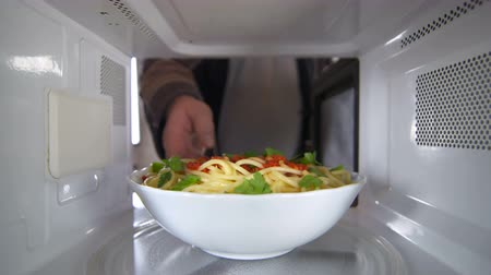 reheating : Man wearing a robe heating up cooked pasta dish with tomato sauce in the microwave oven at residential kitchen view inside the microwave Stock Footage