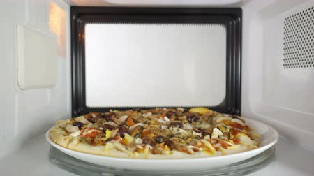 reheating : Baked seafood pizza Frutti di Mare reheating in microwave oven inside view version with external lighting