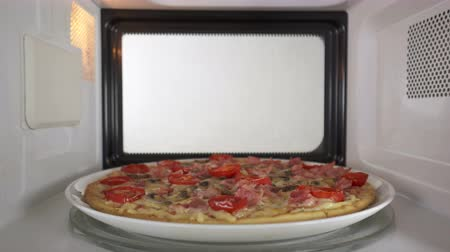 reheating : Baked mushroom ham pizza heating in microwave oven inside view