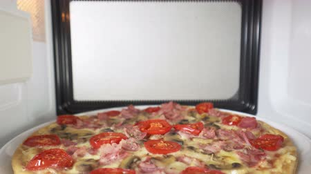 reheating : Tasty pizza topped with tomato mushroom and ham heating in microwave oven. Inside view