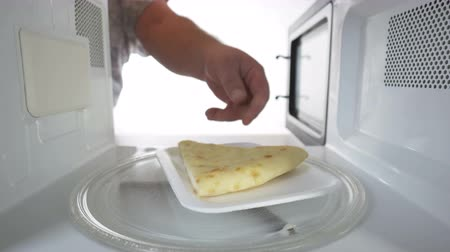 leftover : Reheating leftover slice of cheese pie on supermarket tray in the microwave oven Stock Footage