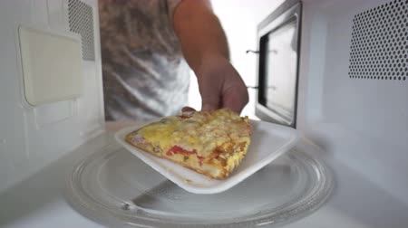 reheat : Reheating leftover slice of pizza in microwave man putting plastic plate with pizza in the oven