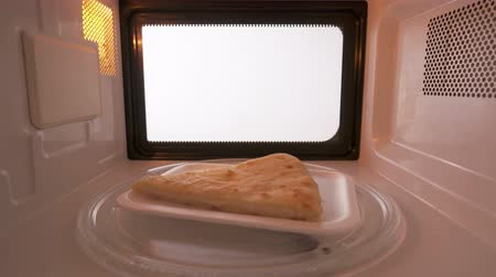 leftover : Plastic plate with slice of cheese pie spinning on turntable in the microwave oven. Version without external lighting for more natural look. Stock Footage