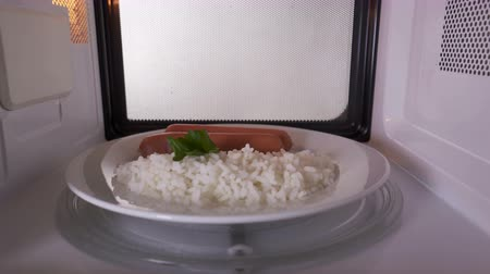 reheat : Rice with sausages on a plate heating in the microwave oven inside view. Version with external lighting