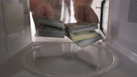 dolar : Man hiding stacks of money in the microwave oven Dostupné videozáznamy
