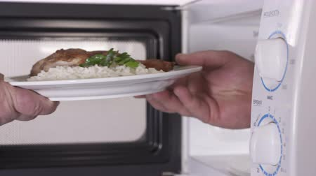 reheat : Personal chef who works in your microwave. Senior woman opens door of microwave to get food out man holds out his hand with a plate. Cooking concept Stock Footage