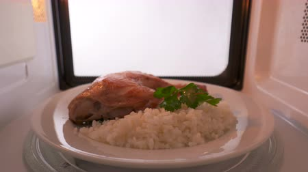 reheat : Perfectly cooked pan fried chicken leg with crispy skin and rice garnish heating in the microwave. Version without external lighting for more natural look Stock Footage