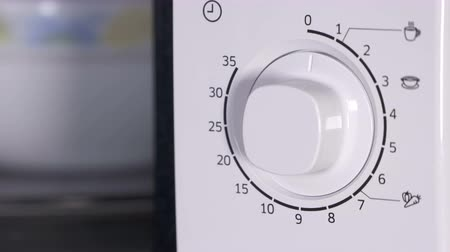 mikrohullámú : Using microwave oven closing door and setting cooking time from one to nine minutes. Sequence, close-up. Stock mozgókép