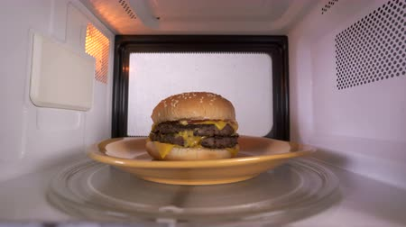 reheat : Reheating cooked double cheeseburger hamburger in the microwave. Tasty hamburger topped with cheese two patties and lettuce microwaving inside oven.