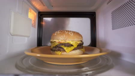 reheat : Young girl using microwave for reheating cooked double cheeseburger. Tasty and appetizing hamburger topped with cheese two patties and lettuce heating up in oven. Girl looks inside and takes out heated sandwich.