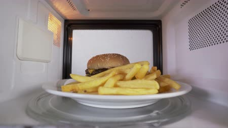 reheat : Reheating a double cheeseburger with french fries in the microwave. Tasty hamburger topped with cheese two patties lettuce and crispy french fries inside microwave. Stock Footage