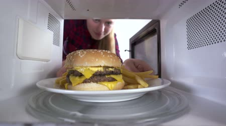 reheat : Girl using microwave to reheat food. Double hamburger with french fries reheating inside microwave oven