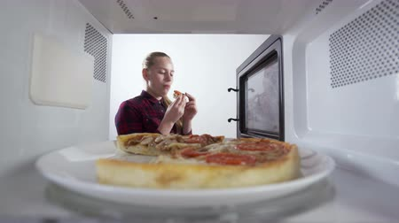reheat : Young girl eats a slice of pizza just reheated in the microwave. View through the oven.