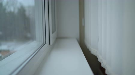 persiana : Window with vertical blinds and falling snow outside. Shallow DOF