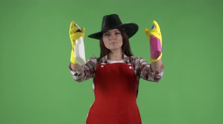 houseclean : Woman pulling on rubber gloves holding two glass cleaners as guns against green screen. House cleaning service worker or housewife spraying detergent at the camera making gestures like a cowboy