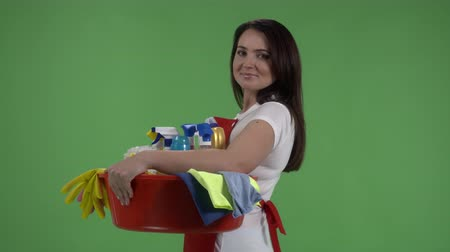 houseclean : House cleaning service. Woman holds washbowl with washing fluids and rags against green screen.