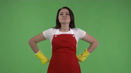 houseclean : Woman as house cleaning service worker or housewife pulling on rubber gloves ready for cleaning against green screen.