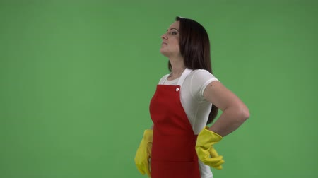 houseclean : Serious housewife pulling on rubber gloves ready for cleaning against green screen Stock Footage