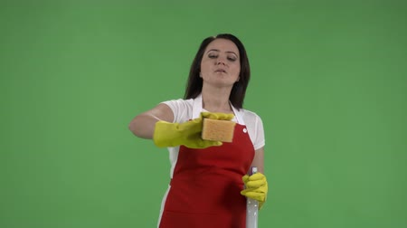houseclean : Cleaning service worker or housewife with cleaning supplies against green screen
