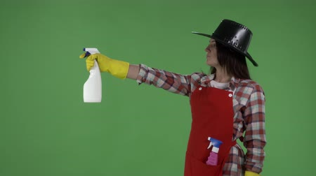 houseclean : Housewife like a cowboy doing housework spraying detergent against green screen. House cleaning service worker or housemaid in protective gloves holding glass cleaner as gun. Stock Footage