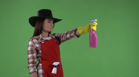 houseclean : Woman while cleaning the house makes gestures like a cowboy with a gun against green screen. Cleaning service worker or housemaid in protective gloves spraying detergent in slow motion.