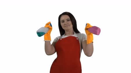 sprzataczka : Woman pulling on rubber gloves holding two glass cleaners as guns on white background. Housewife spraying detergent at the camera making gestures like a cowboy. 4k footage PNG with alpha channel