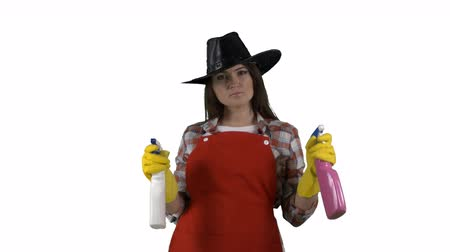 houseclean : Woman pulling on rubber gloves holding two glass cleaners as guns against green screen. Housewife spraying detergent at the camera making gestures like a cowboy. 4k footage PNG with alpha channel