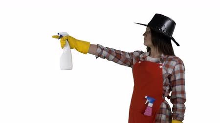houseclean : Woman while cleaning the house makes gestures like a cowboy with a gun on white background. Cleaning service worker or housemaid spraying detergent in slow motion. 4k footage PNG with alpha channel