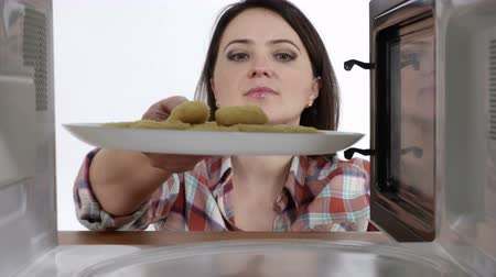 reheat : Woman heating fast food in the microwave at home. Rotating chicken nuggets inside microwave oven
