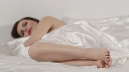 ленивый : Young brunette woman falling asleep on white linen in bed Стоковые видеозаписи