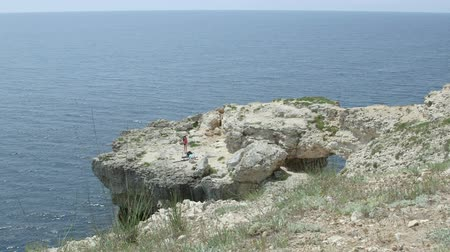 platform edge : Young women dancers installing portable dancing pole on a rock by the sea Stock Footage