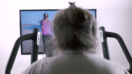 elliptical : Obese senior woman working out on elliptical trainer in front of the television. TV screen displaying jogging workout of a young fit girl.