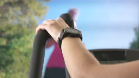 elliptical : Woman listening to music with smart watch during cardio workout on elliptical trainer in front of TV