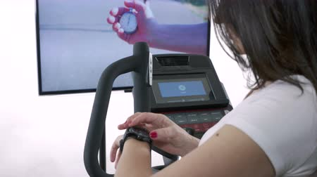 elliptical : Woman wearing smart watch preparing for cardio exercise on elliptical trainer in front of the TV. Television screen displaying fitness video for joggers. Hand with stopwatch, fit girl running.
