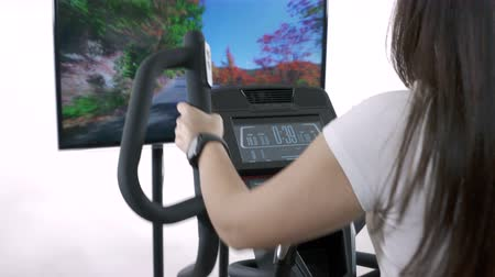 elliptical : Woman wearing smart watch exercising on elliptical trainer in front of the TV. Television screen displaying video of young girl jogging.
