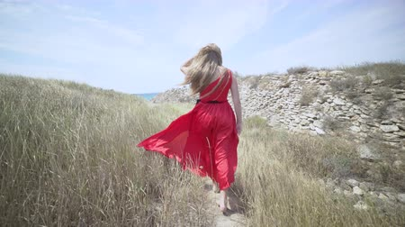 mar vermelho : Young girl in red dress walking barefoot on the footpath towards the sea. Girls long hair and bright scarlet gown blowing in the wind. Gimbal steadicam shot Vídeos