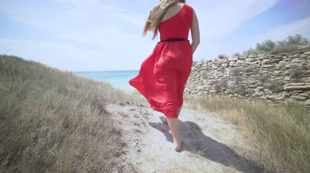 ventoso : Young girl in red dress walking barefoot on a path towards the sea. Girls long hair and bright scarlet gown blowing in the wind. Windy summer day at the seaside. Gimbal steadicam shot. Stock Footage