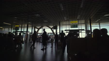 SIMFEROPOL, RUSSIA - CIRCA SEP 2017: Passengers waiting at departure gate to board a flight in the airport terminal. Silhouettes of people with luggage against a window of Simferopol airport