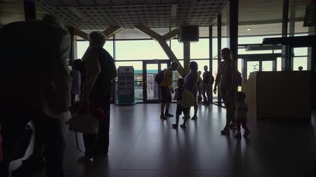 SIMFEROPOL, RUSSIA - CIRCA SEP 2017: People are waiting in the airport terminal to board a plane. Silhouettes of people with luggage at Simferopol international airport.