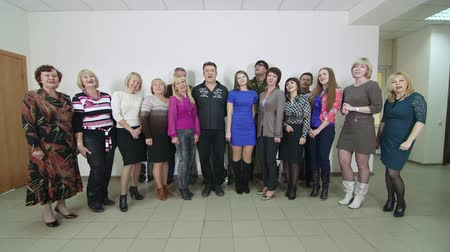 караоке : SIMFEROPOL, CRIMEA - CIRCA OCTOBER 2015: Business colleagues singing together standing in a row in small office lobby.