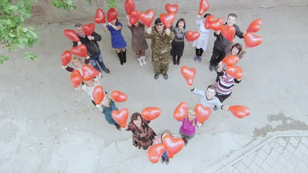 SIMFEROPOL, CRIMEA - CIRCA OCTOBER 2015: Top view group of people with balloons standing as heart shape. Business colleagues looking up and shouting greetings. Stock Footage