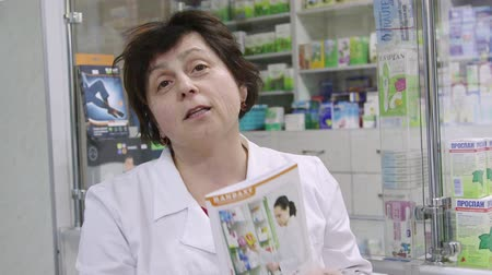 SIMFEROPOL, CRIMEA - CIRCA OCTOBER 2015: Female pharmacist reads brochure with medical advice in the drugstore. Woman health professional talking and looking at the camera. Stock Footage