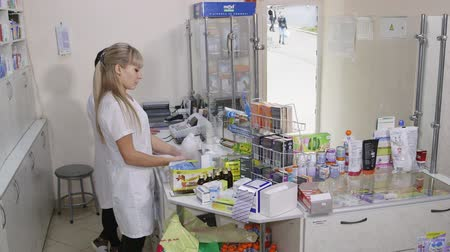 gyógyszerész : SIMFEROPOL, CRIMEA - CIRCA OCTOBER 2015: Female pharmacists working behind the pharmacy counter at the drugstore. Team of pharmacists in white coats near pharmacy shelves with medicines.