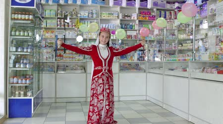SIMFEROPOL, CRIMEA - CIRCA OCTOBER 2015: Pharmacy store interior. Little girl in traditional Crimean Tatar costume performs a dance at the drugstore.