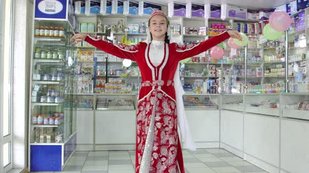 tatar : SIMFEROPOL, CRIMEA - CIRCA OCTOBER 2015: Pharmacy store interior. Little girl in traditional Crimean Tatar costume performs a dance at the drugstore.