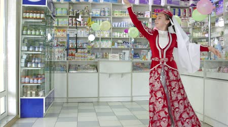SIMFEROPOL, CRIMEA - CIRCA OCTOBER 2015: Pharmacy store interior. Little girl in traditional folk Crimean Tatar clothes performs a dance at the drugstore.