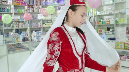 SIMFEROPOL, CRIMEA - CIRCA OCTOBER 2015: Pharmacy store interior. Crimean Tatar girl in delicate national attire performs a dance at the drugstore.