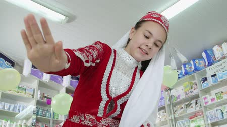 tatar : SIMFEROPOL, CRIMEA - CIRCA OCTOBER 2015: Pharmacy store interior. Crimean Tatar little girl dancing in folk costume at the drugstore. Wideo