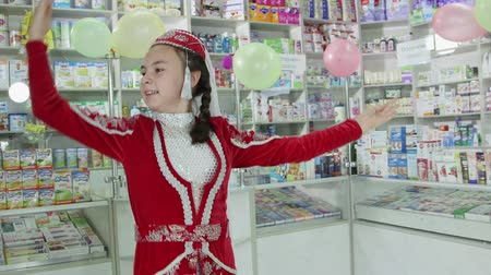 SIMFEROPOL, CRIMEA - CIRCA OCTOBER 2015: Pharmacy store interior. Crimean Tatar little girl dancing in folk costume at the drugstore. Stock Footage